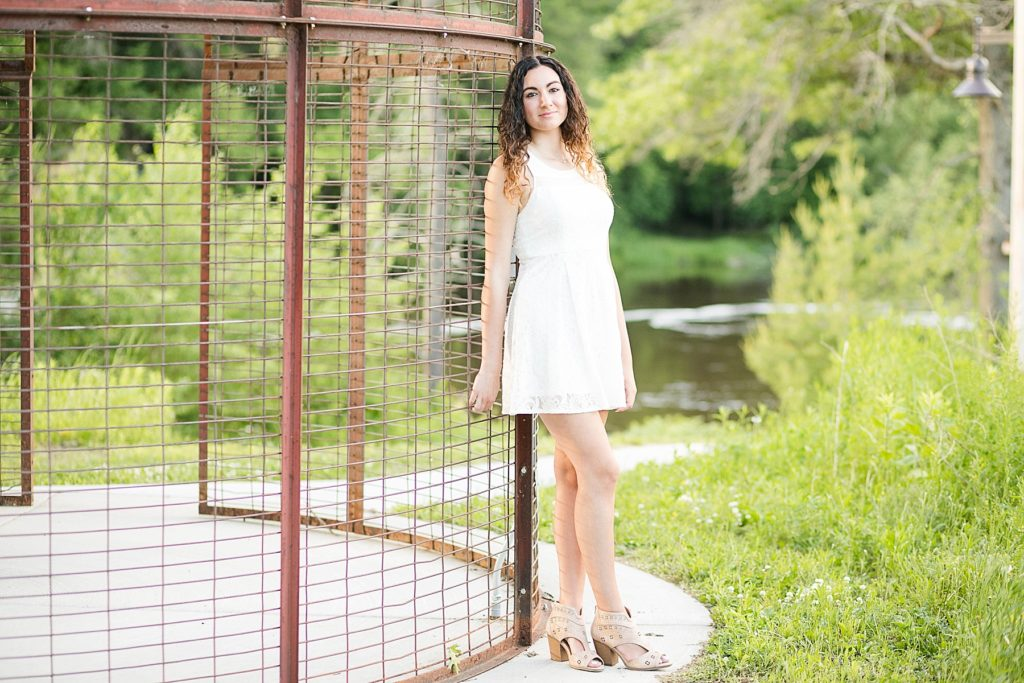 girl in a white dress leaning on a corn crib  for her Eau Claire senior photos