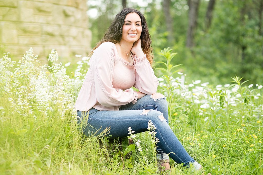 girl sitting in wildflowers in a pink top and ripped jeans for her Eau Claire senior photos
