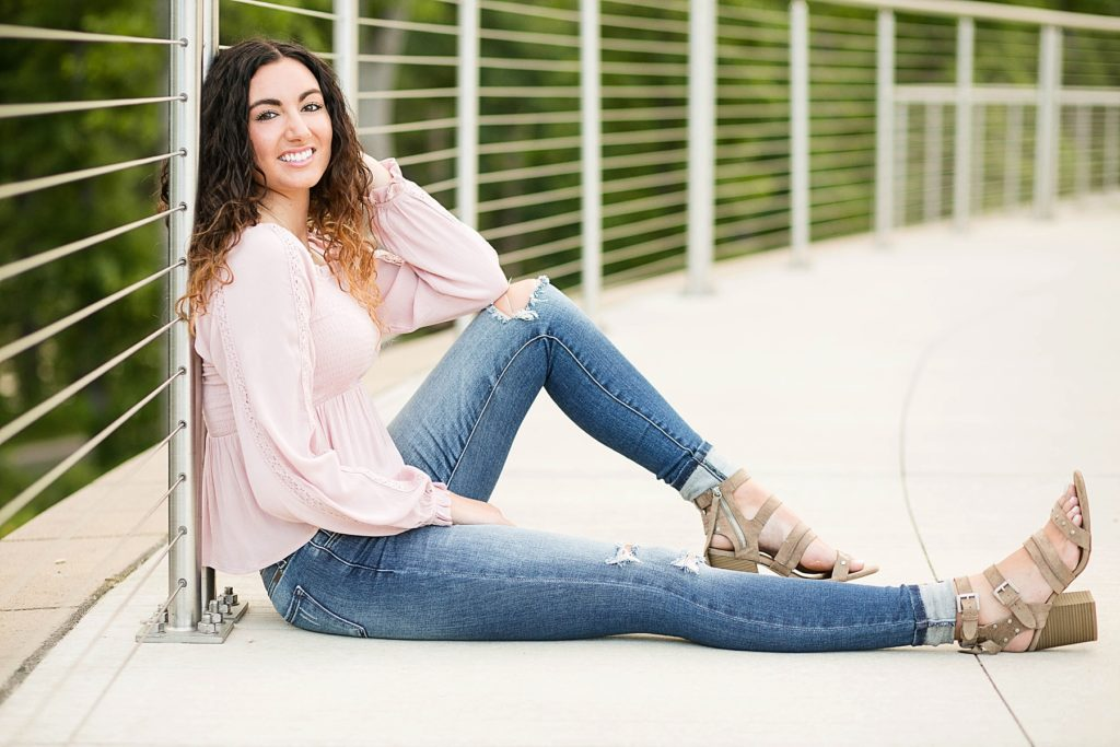 girl in a pink top and ripped jeans with tan heels leaning against a wire railing for her Eau Claire senior photos