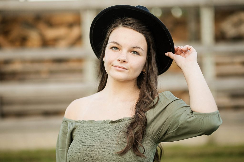 girl at a farm with a black hat on for her boho senior session in Eau Claire, WI