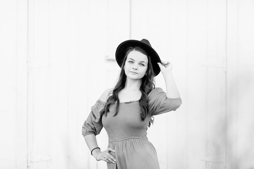 girl in a black and white photo holding onto a black hat  for her boho senior session in Eau Claire, WI