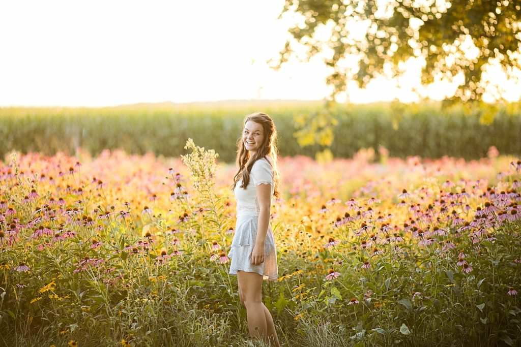 girl in a field of wildflowers for her boho senior session in Eau Claire, WI