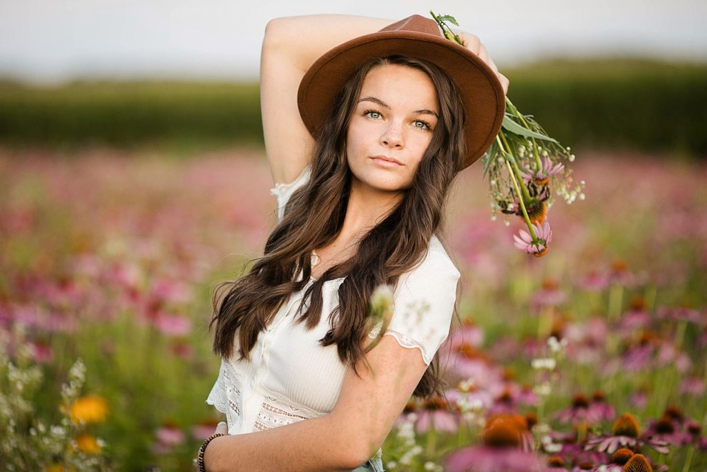 girl holding flowers with a brown hat on in a field of wildflowers for her boho senior session in Eau Claire, WI
