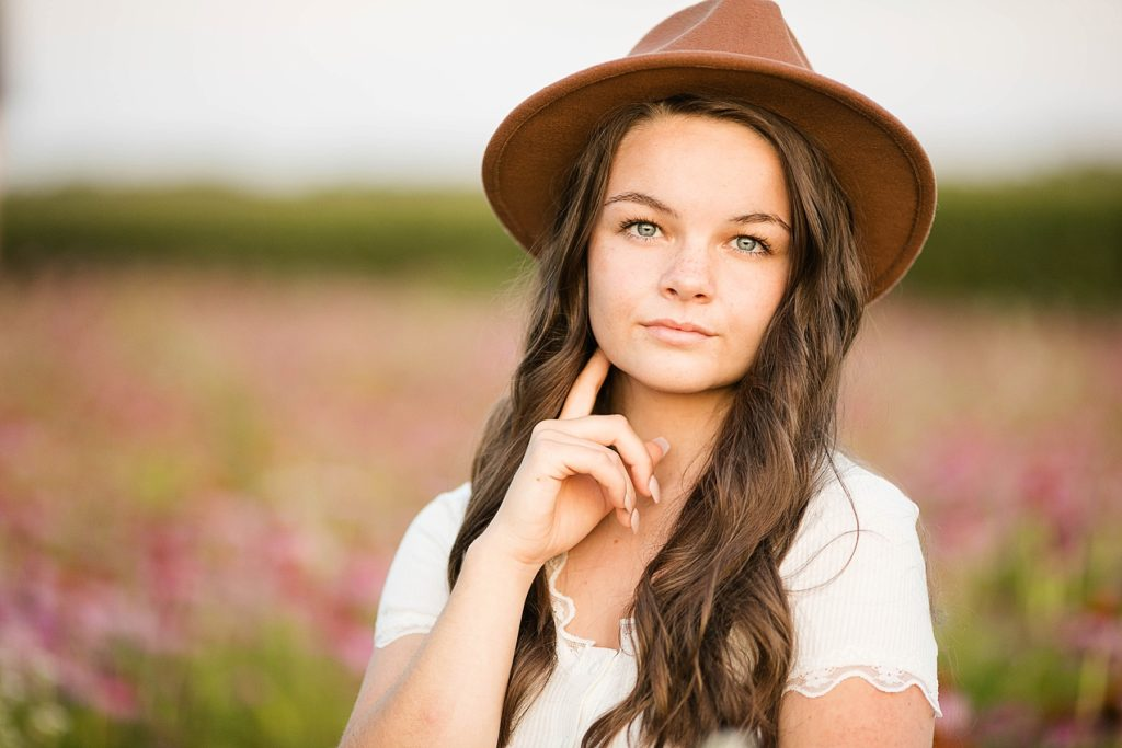 girl with a brown hat on in a field of wildflowers for her boho senior session in Eau Claire, WI
