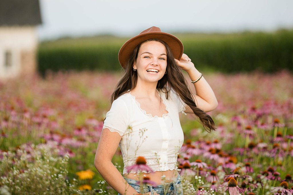 spinning in a field of wildflowers for her boho senior session in Eau Claire, WI