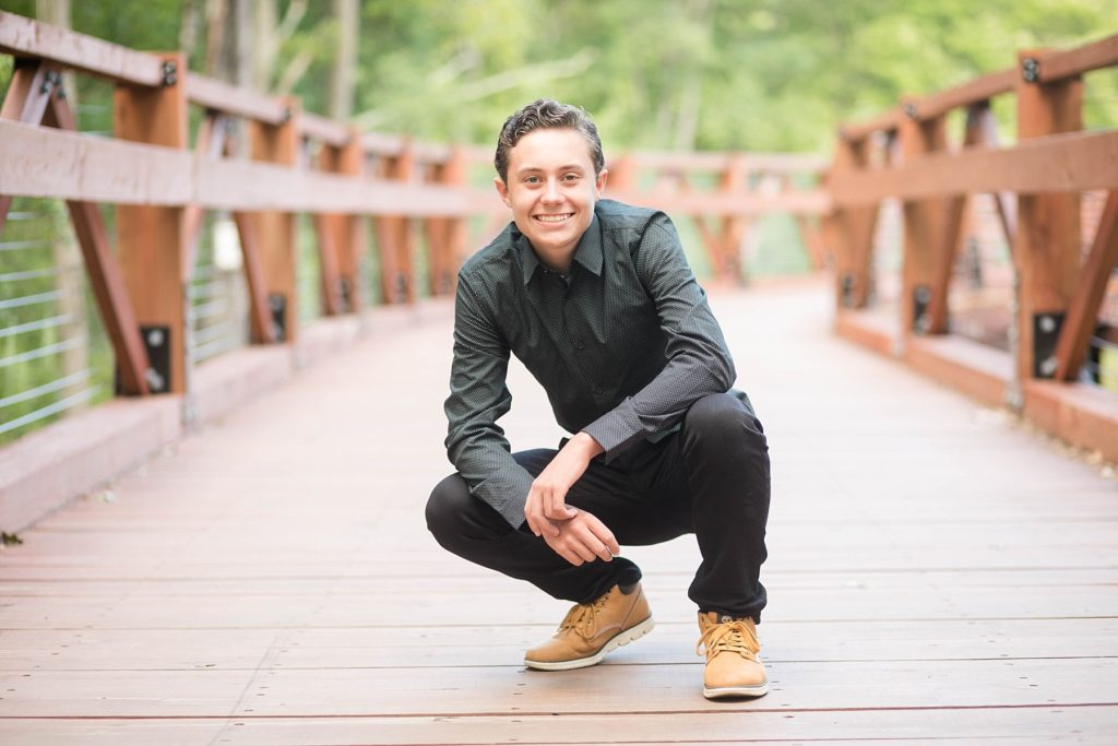 boy crouching on a bridge in a black button up shirt and black jeans at Irvine Park for his senior photos in Chippewa Falls, WI