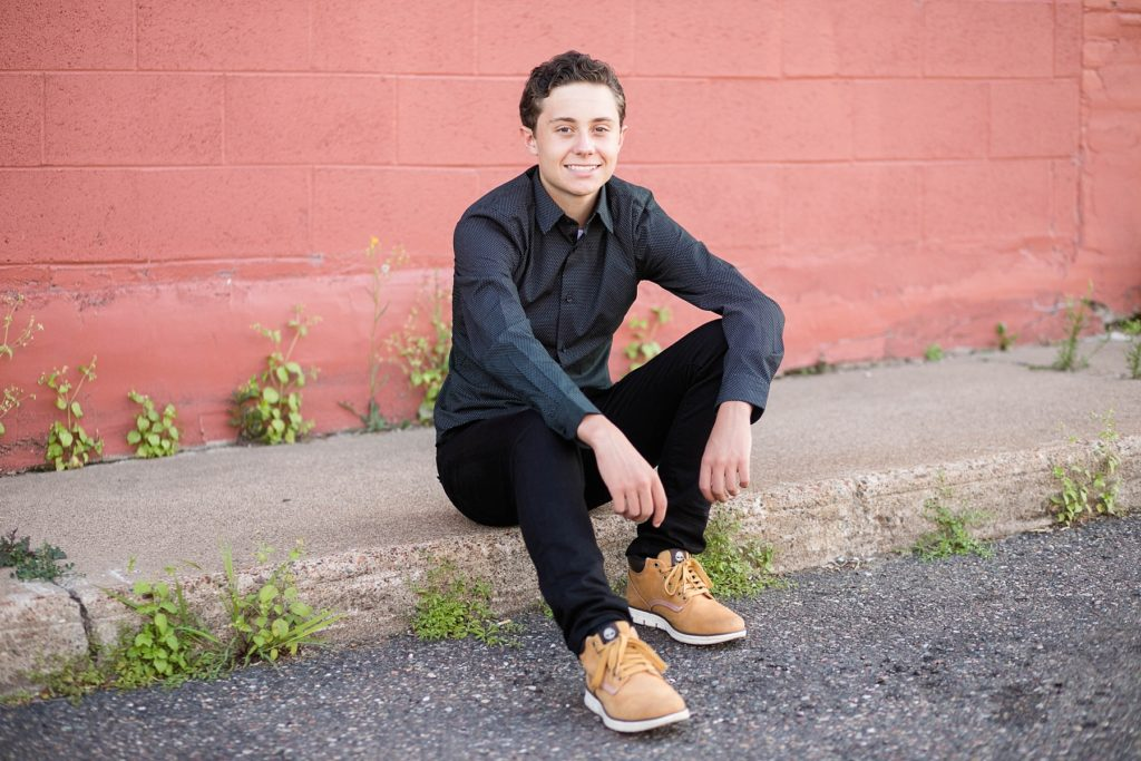 boy sitting on the curb infront of a red wall in a black outfit downtown Chippewa Falls for his senior pictures