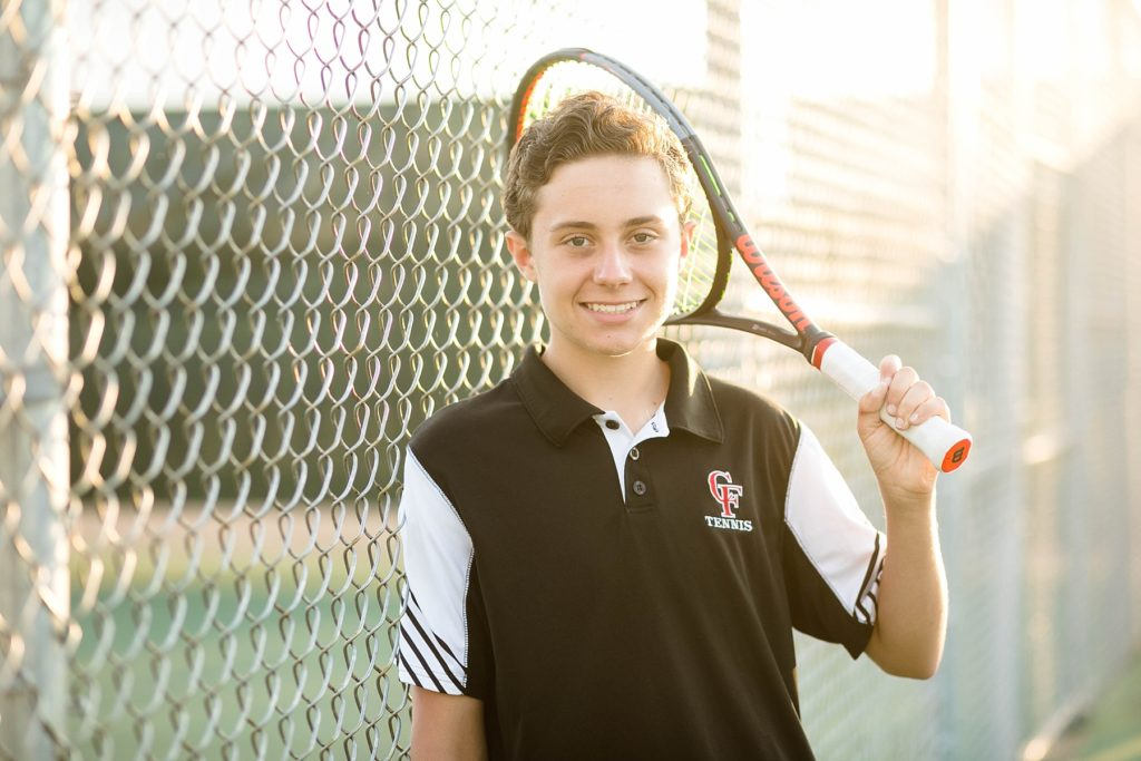 boy with a chippewa falls high school tennis polo on holding his tennis racquet at chi hi on the tennis court for his senior photos