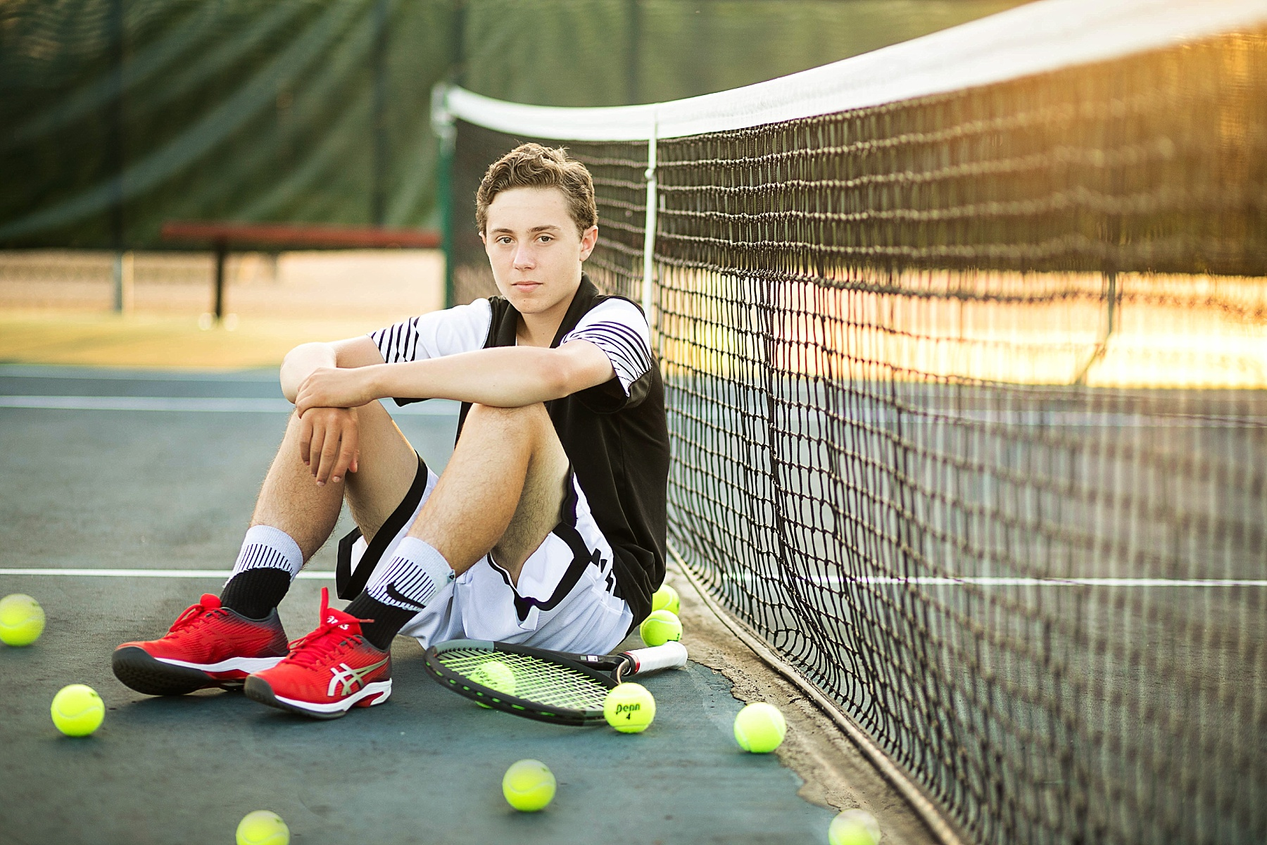 boy sitting against a tennis net at chi hi with his uniform on and tennis balls around him