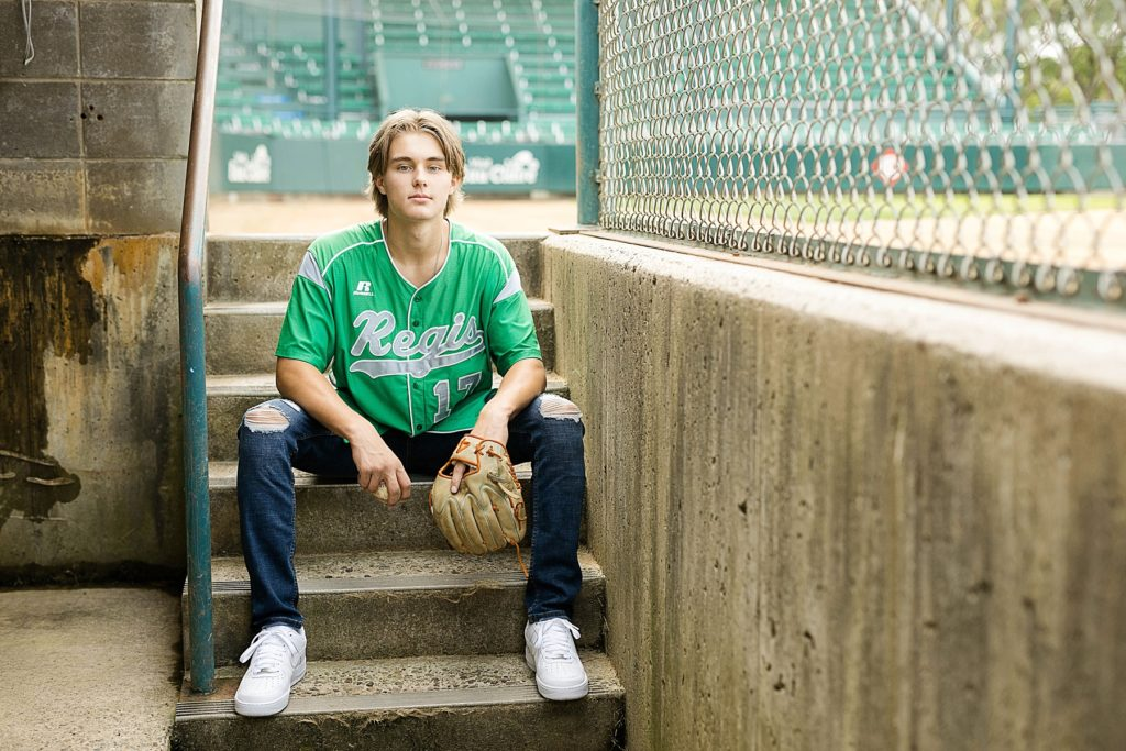 boy sitting in dugout with a green Regis High School baseball jersey on in Carson Park in Eau Claire for his senior photos