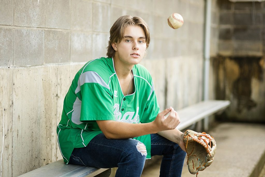 boy sitting in dugout with a green Regis High School baseball jersey on  throwing a ball in Carson Park in Eau Claire for his senior photos