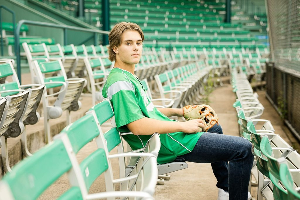 boy sitting in stands with a green Regis High School baseball jersey on in Carson Park in Eau Claire for his senior photos