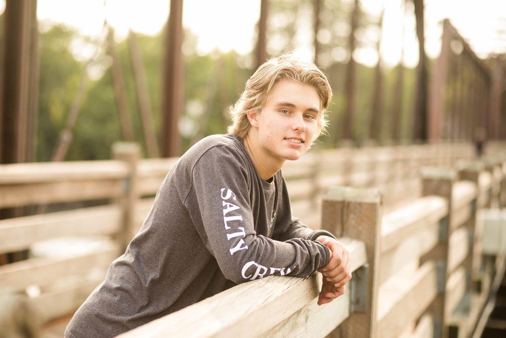 boy leaning on the trestle bridge in Phoenix Park for his senior photos in Eau Claire