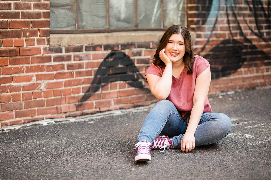 Girl sitting in front of graffiti on a brick wall in Eau Claire for her laid back senior photos