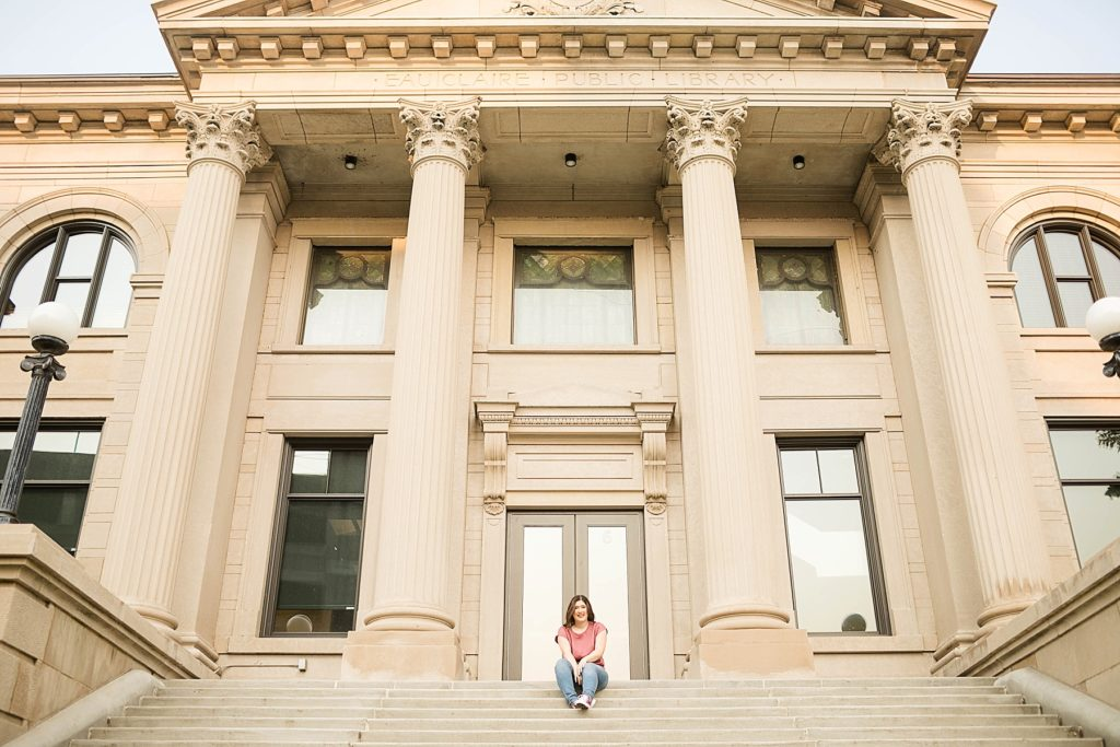 girl sitting on the staircase of the Eau Claire courthouse in Eau Claire for her laid back senior photos