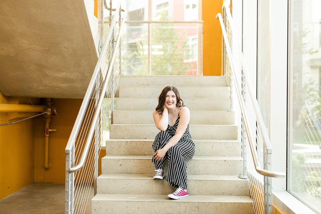girl sitting on concrete stairs with yellow walls in Eau Claire for her laid back senior photos