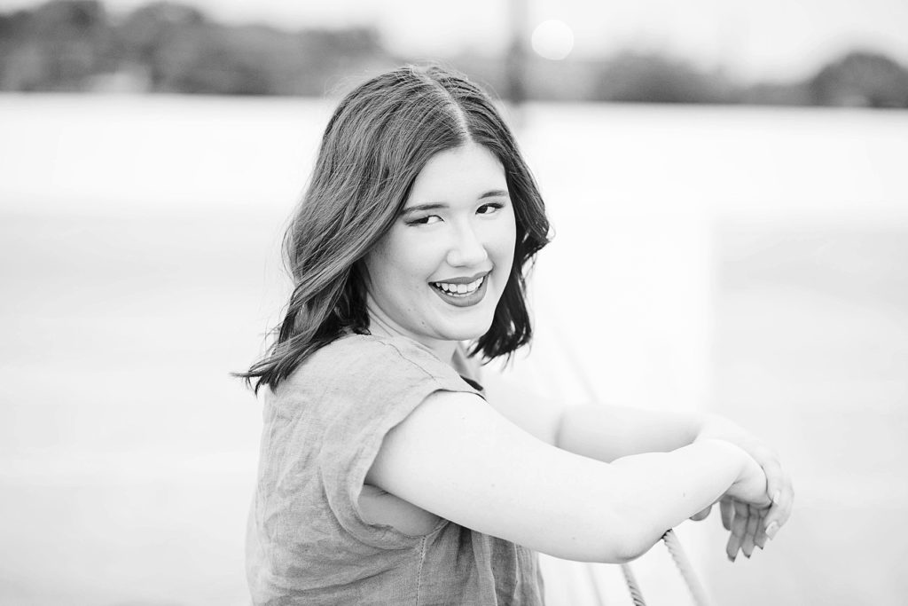 girl smiling at the camera in a black and white photo in Eau Claire for her laid back senior photos