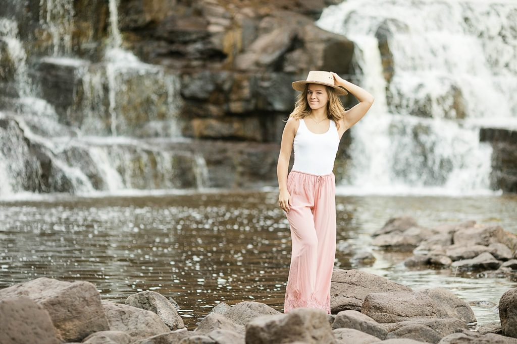 girl standing in rocks below Gooseberry Falls for her North Shore senior photos on Lake Superior