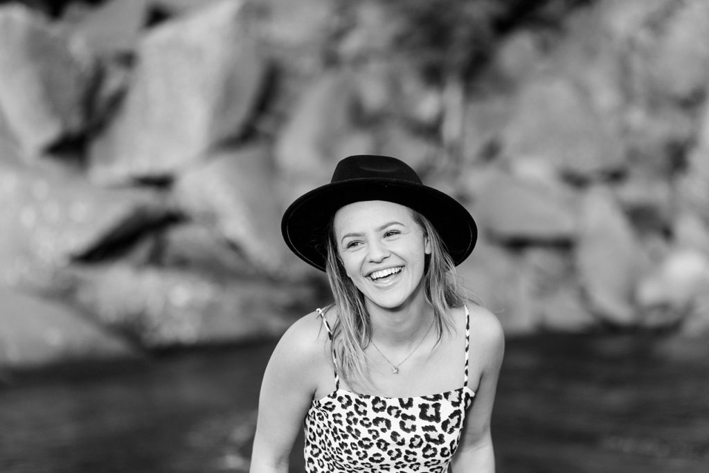 girl laughing in a black and white photo with a black hat on Black Sand Beach in Silver Bay, MN for her senior photos