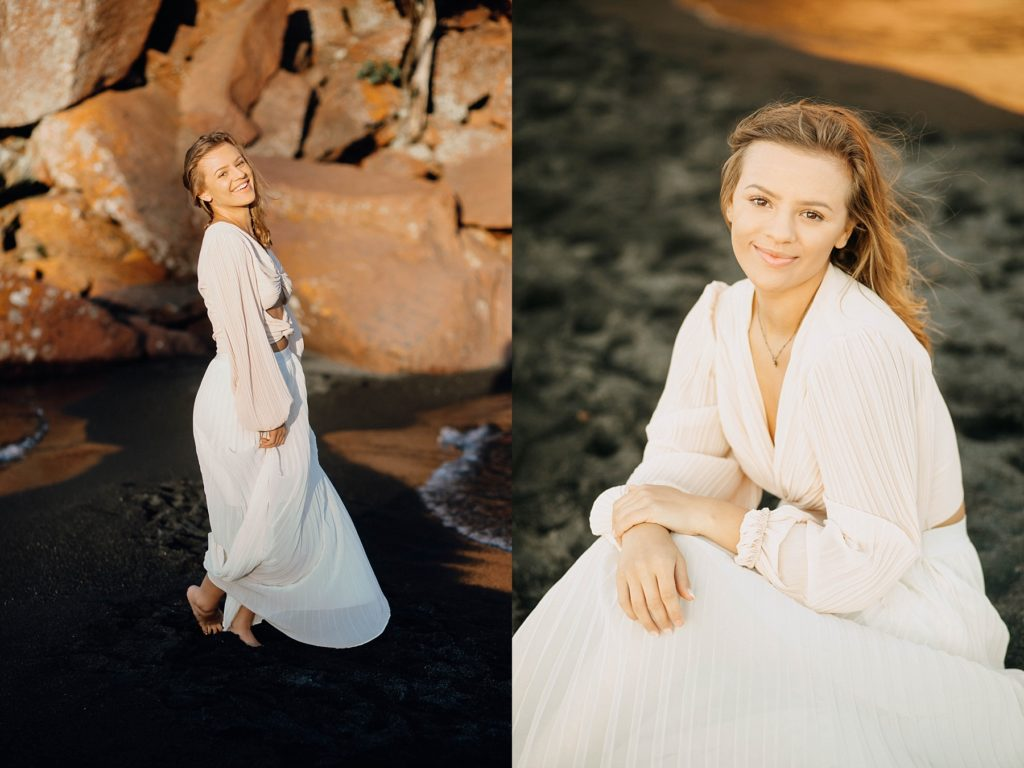 girl sits in on a black sand beach on Lake Superior with a blowing dress on for her North Shore senior pictures
