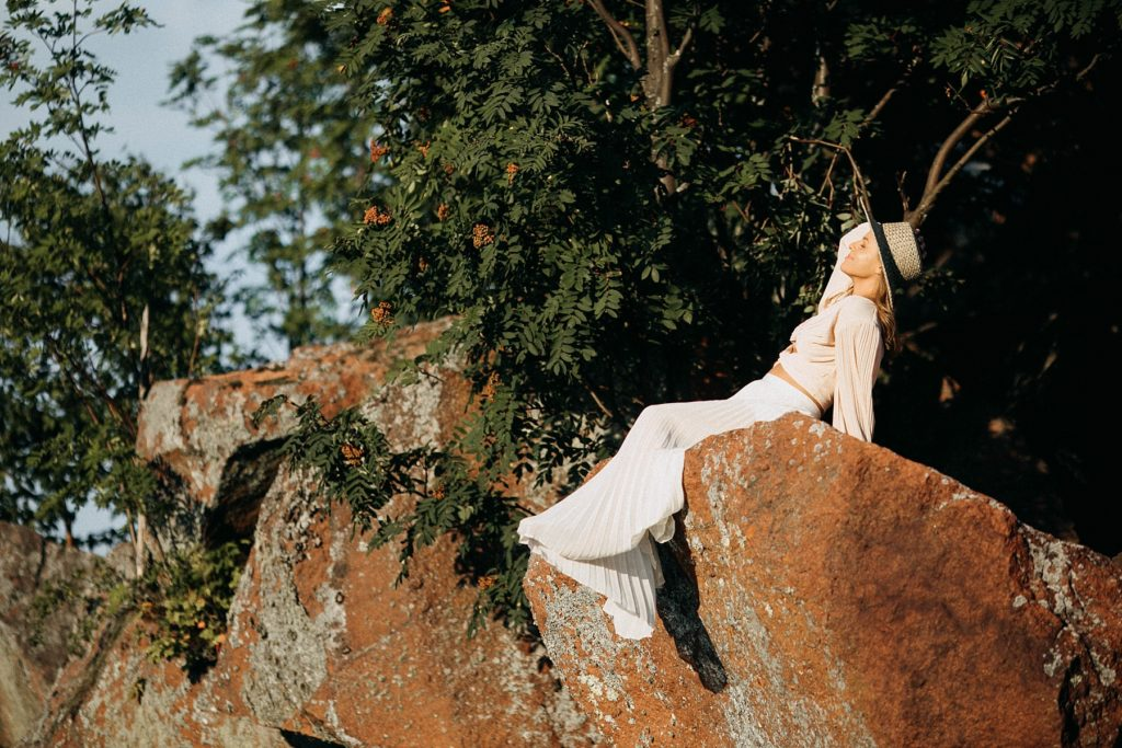 girl sits on rocks above Black Sand beach for her senior photos in Silver Bay, MN