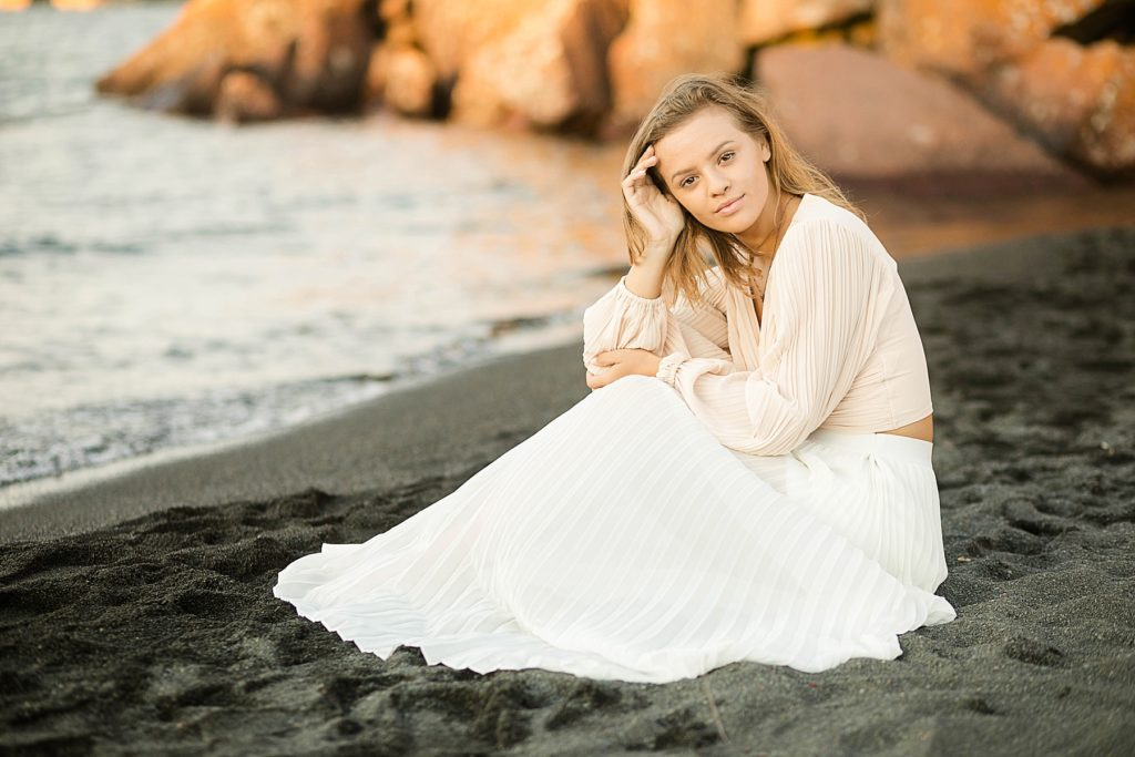 girl sits in on a black sand beach on Lake Superior with a gown on for her North Shore senior pictures
