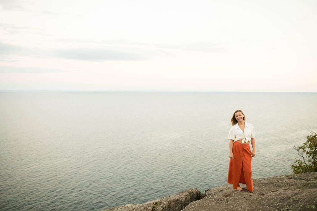 girl standing on rocks at Palisade head in an orange skirt and crop top for her boho senior photos on Lake Superior