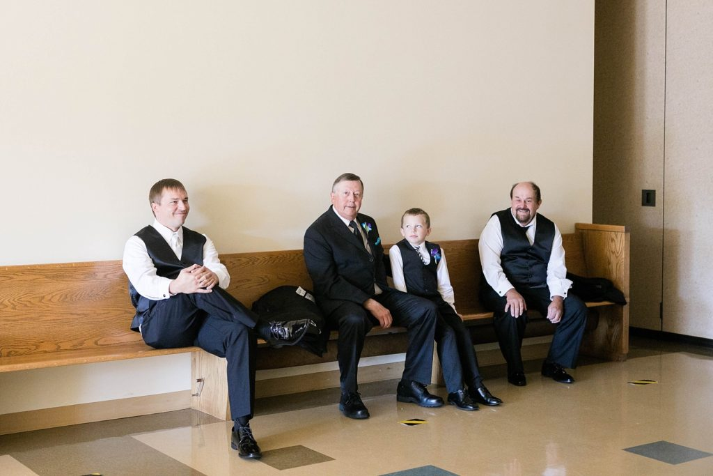 groom and fathers sitting and waiting for the ceremony to start at Immaculate Conception Church in Eau Claire