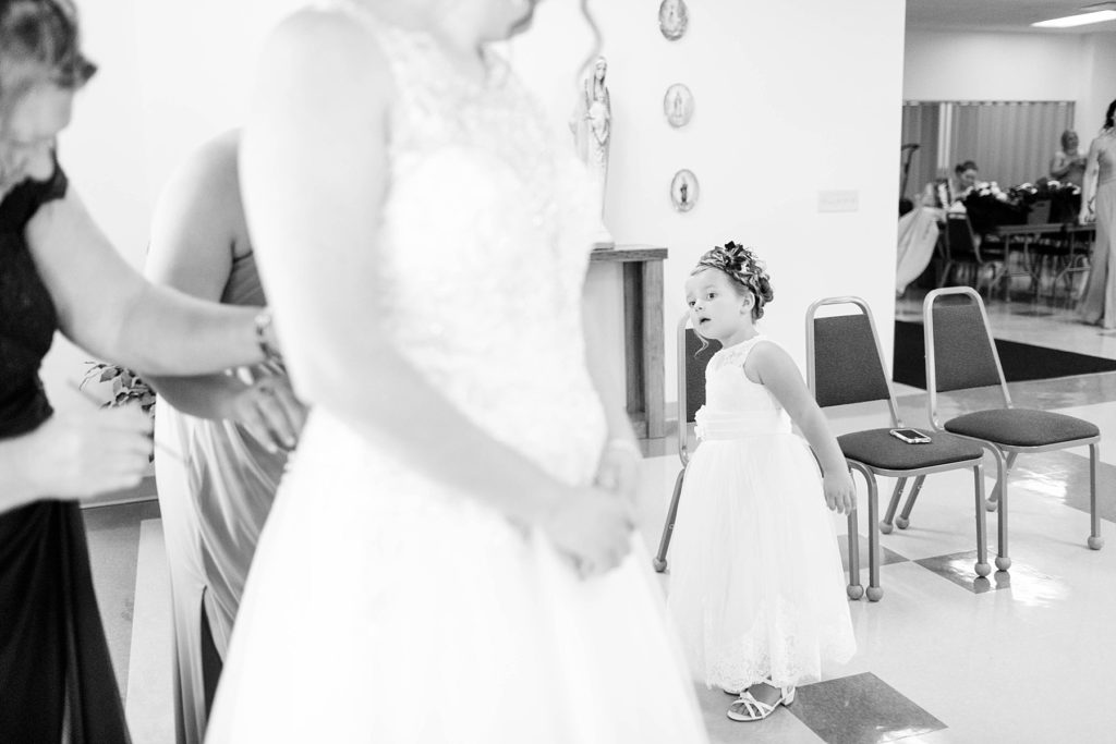 flower girl looking at the bride getting into her gown at Immaculate Conception Church in Eau Claire