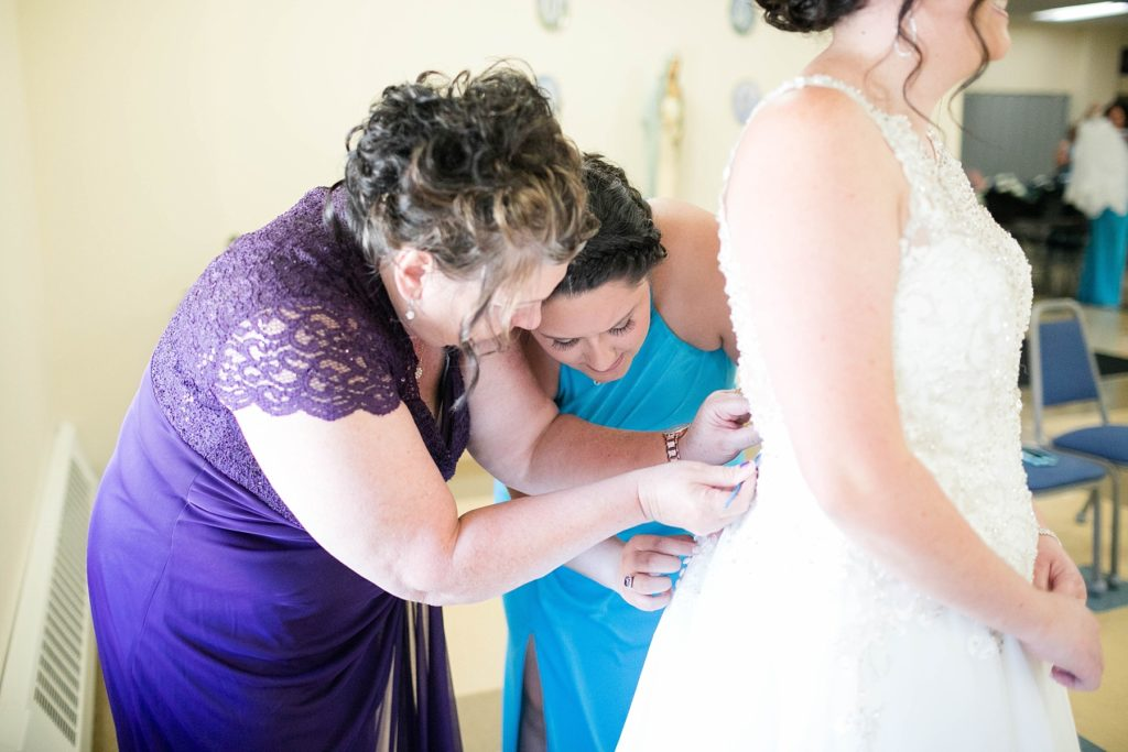 brides mom and sister buttoning her gown at Immaculate Conception Church in Eau Claire