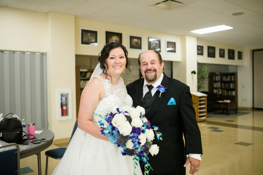 bride and her father smiling for the camera before walking her down the aisle at Immaculate Conception Church in Eau Claire