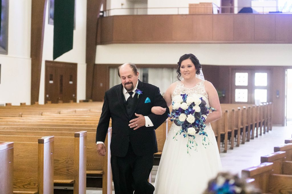 father walking daughter down the aisle at a small wedding at Immaculate Conception Church in Eau Claire