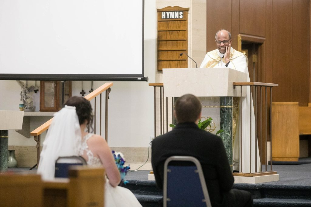 priest smiling at the couple during the homily at Immaculate Conception Church in Eau Claire