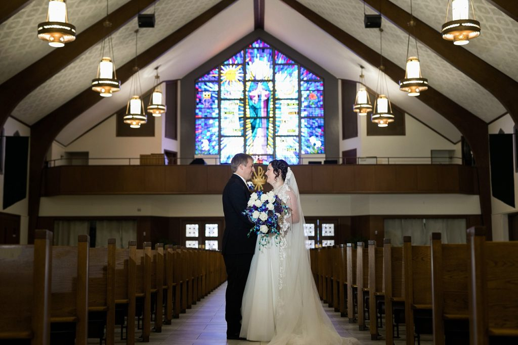 low light portrait of the bride and groom in an empty sanctuary at Immaculate Conception Church in Eau Claire