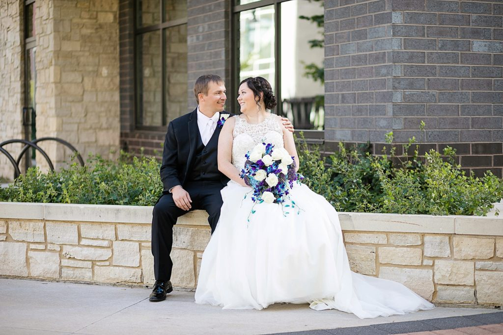 bride and groom sitting on a wall at Eau Claire micro wedding in Phoenix Park