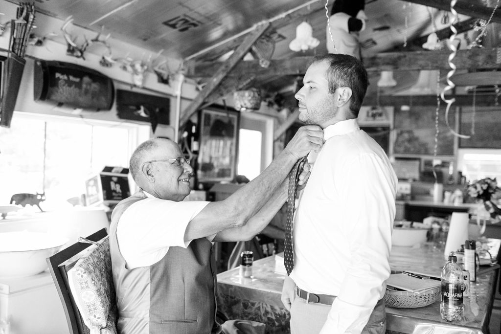 groom's father adjusting his tie at intimate childhood home wedding in Ladysmith, WI