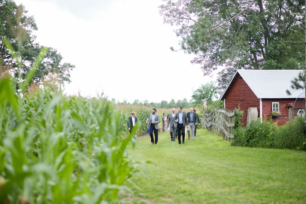 guests walking to the hidden wedding ceremony site at a boho wedding in Wisconsin