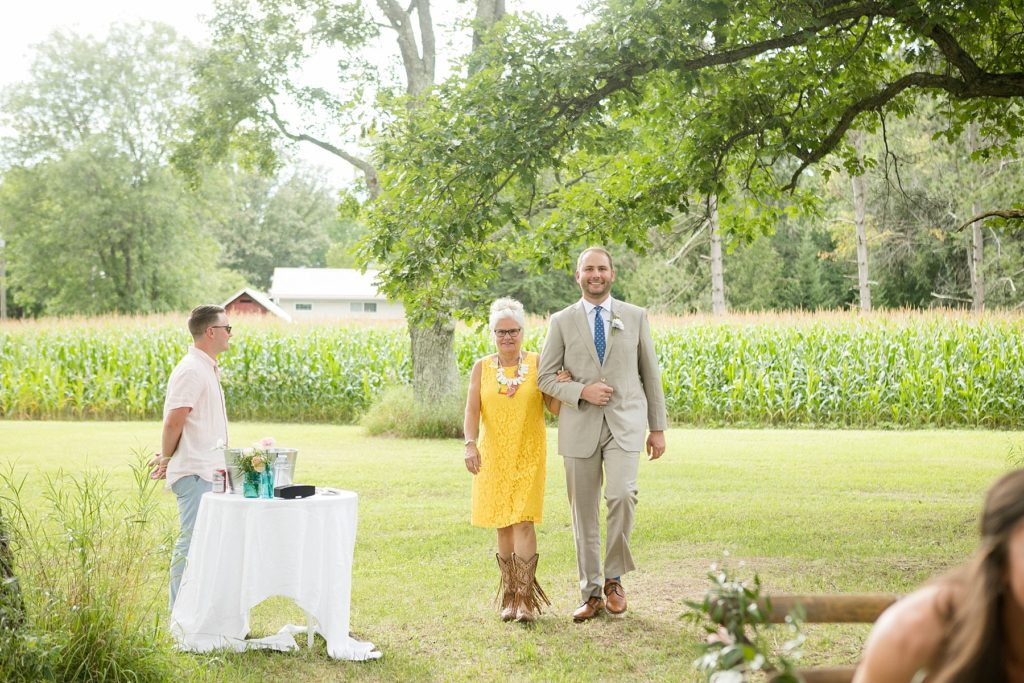 groom walking down the aisle in boho wedding with triangle arch and rug in Ladysmith, WI