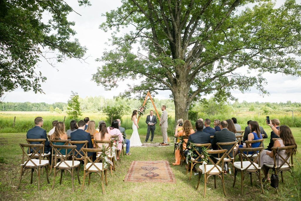 boho wedding with triangle arch and rug in Ladysmith, WI