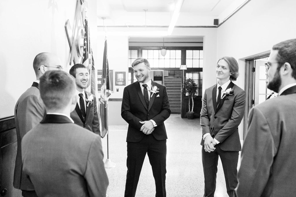 groom and groomsmen talking  at Masonic Ballroom in Eau Claire
