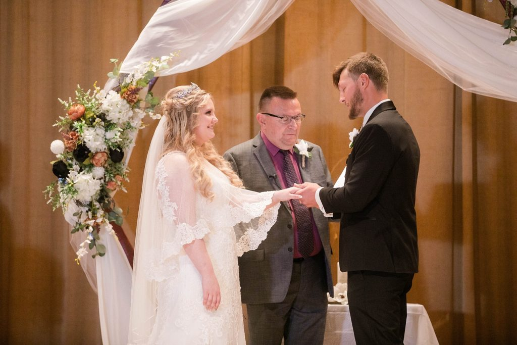 couple exchanging rings at their wedding ceremony  at Masonic Ballroom in Eau Claire
