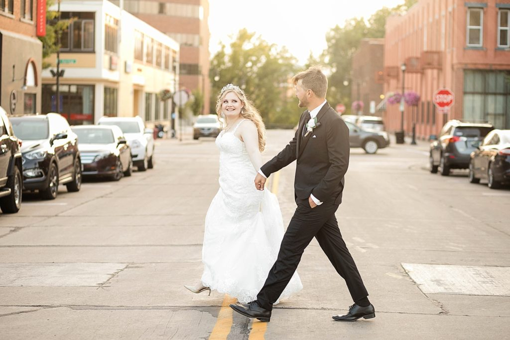 couple on their wedding day crossing the street in downtown Eau Claire