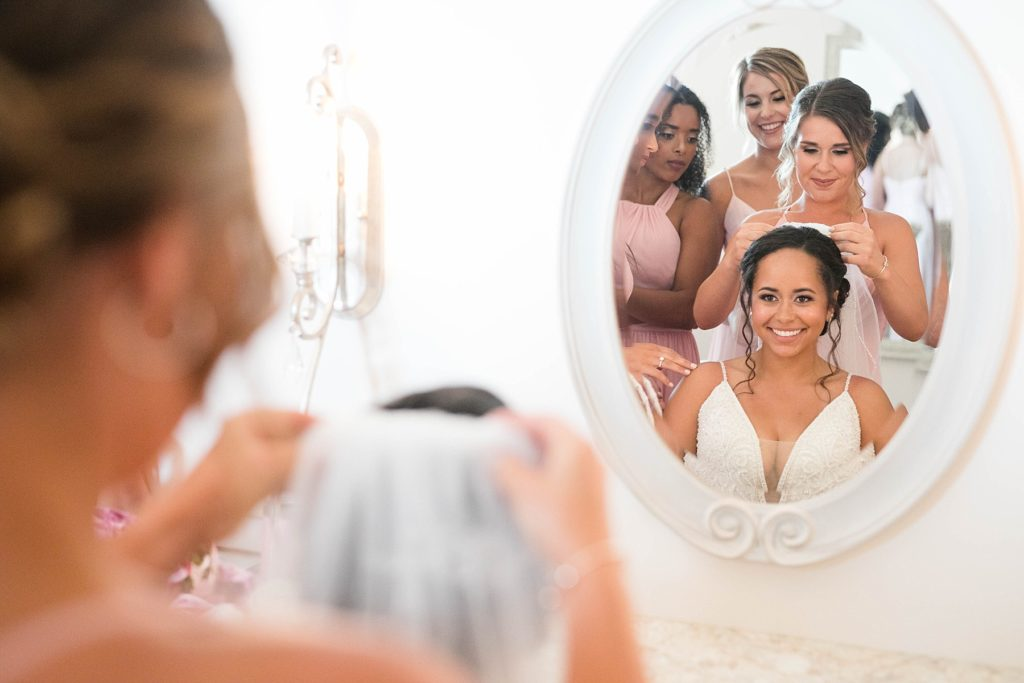 bridesmaids placing the brides veil in looking in a mirror at Lilydale in Chippewa Falls, WI