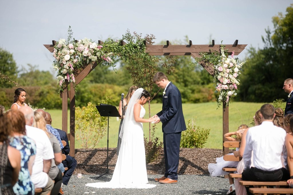 couple holding hands during outdoor wedding ceremony at Lilydale in Chippewa Falls, WI