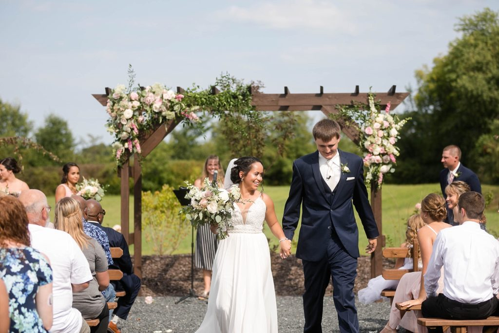 couple walking out of outdoor ceremony with arch behind them and floral at Lilydale in Chippewa Falls, WI
