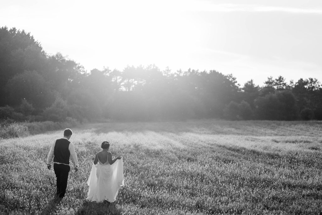 groom holding bride in a field in a black and white photo at Lilydale in Chippewa Falls, WI