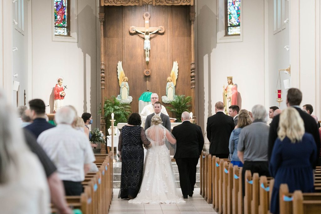 father and mother walk daughter down the aisle to her future husband at St. Charles of Borromeo in Chippewa Falls for their wedding