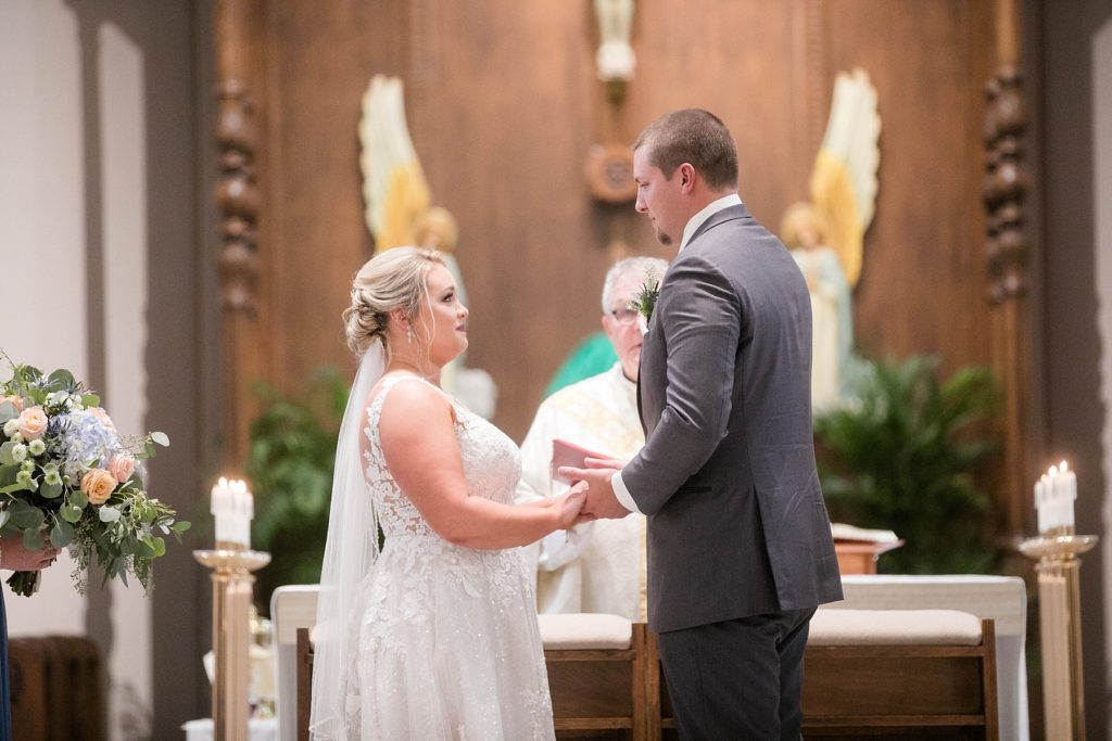 couple share their wedding vows and wedding rites at St. Charles of Borromeo in Chippewa Falls for their wedding