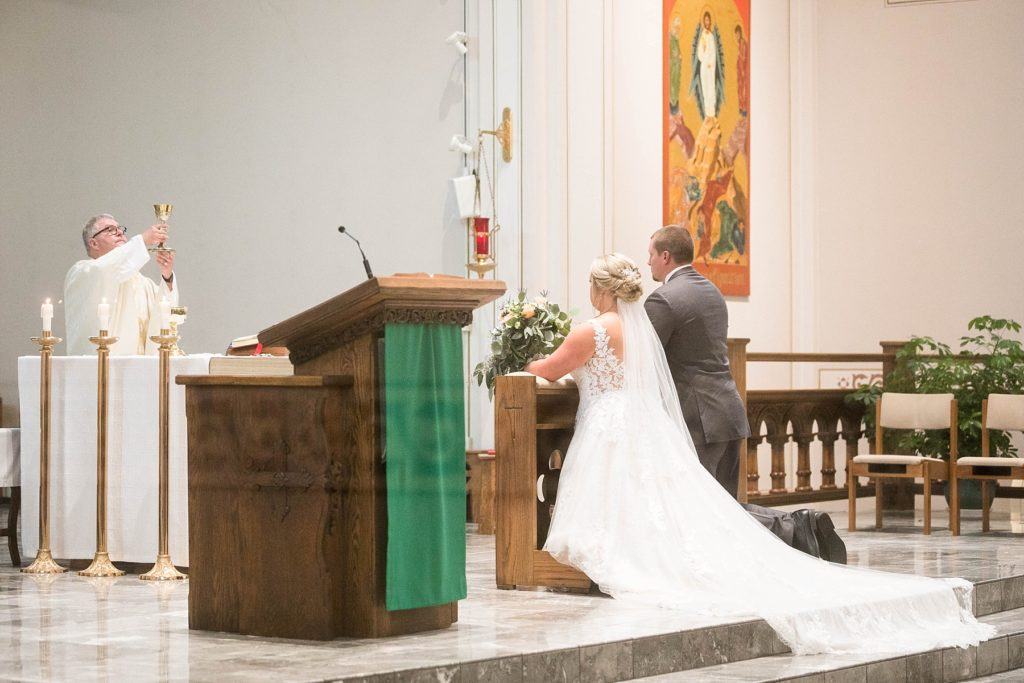 couple during communion at St. Charles of Borromeo in Chippewa Falls for their wedding