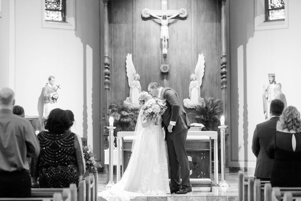 couple share their first kiss in a black and white photo at St. Charles of Borromeo in Chippewa Falls for their wedding